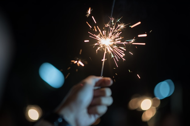 Hand hält ein brennendes wunderkerzenlicht Kostenlose Fotos