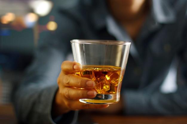 Hand hält ein glas whisky Premium Fotos