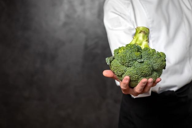 Hand hält einen blümchen brokkoli Premium Fotos