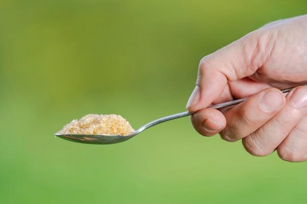 Hand hält einen löffel mit zucker auf einem natürlichen hintergrund Premium Fotos
