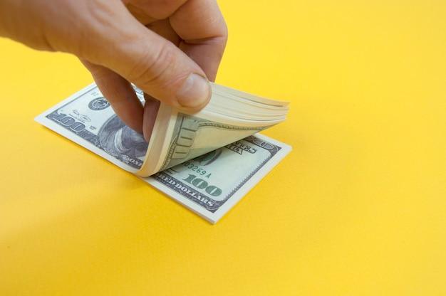 Hand hält einen stapel von hundert dollarnoten Premium Fotos