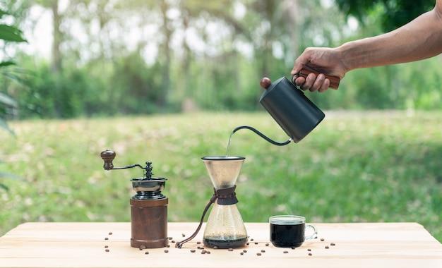 Hand hält einen wasserkocher und gießt heißes wasser für kaffee machen Premium Fotos