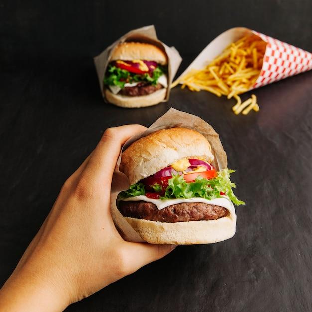Hand hält hamburger Kostenlose Fotos