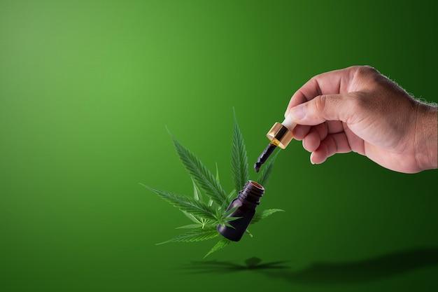 Hand hält pipette mit cannabisöl über eine flasche formula cbd thc. Premium Fotos