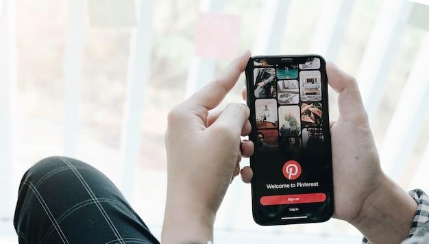 Hand hält smartphone mit pinterest app auf dem bildschirm. pinterest ist eine online-pinnwand, mit der menschen ihre interessanten dinge anheften können Premium Fotos