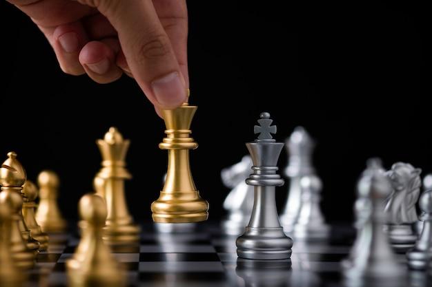 Hand halten und goldenes königschach zum silbernen schach bewegen. Premium Fotos