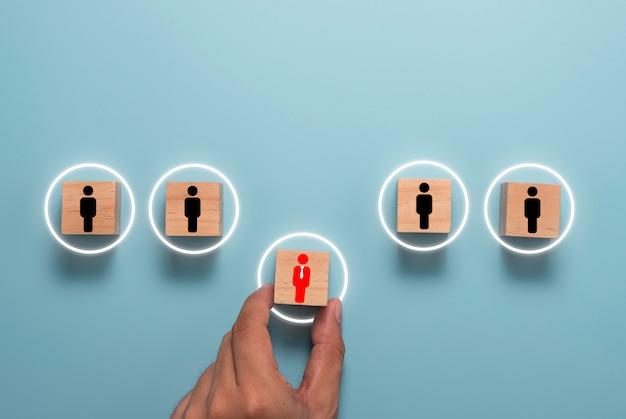 Hand halten und rotes manager-symbol auf holzwürfelblock zwischen schwarzen untergeordneten mitarbeitern bewegen. konzept zur menschlichen entwicklung und förderung. Premium Fotos