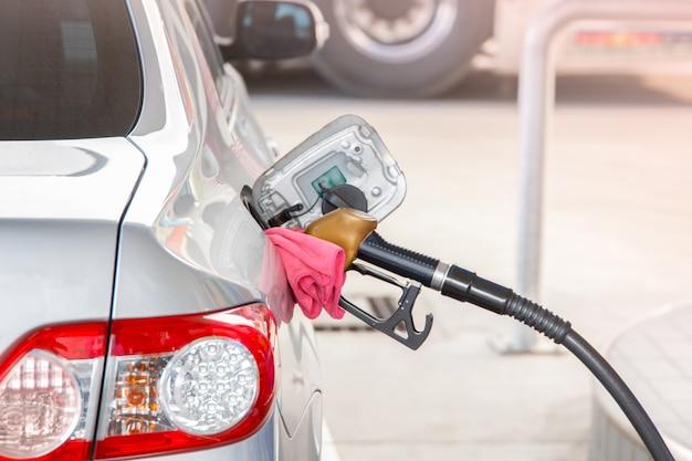 Hand halten zapfpistole, um kraftstoff im auto an der tankstelle hinzuzufügen. Premium Fotos
