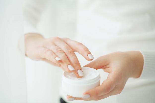 Hand hautpflege. schließen sie oben von den weiblichen händen, die cremerohr, schönheits-hände mit den natürlichen manikürenägeln halten, die kosmetische handcreme auf weicher seidiger gesunder haut auftragen Premium Fotos