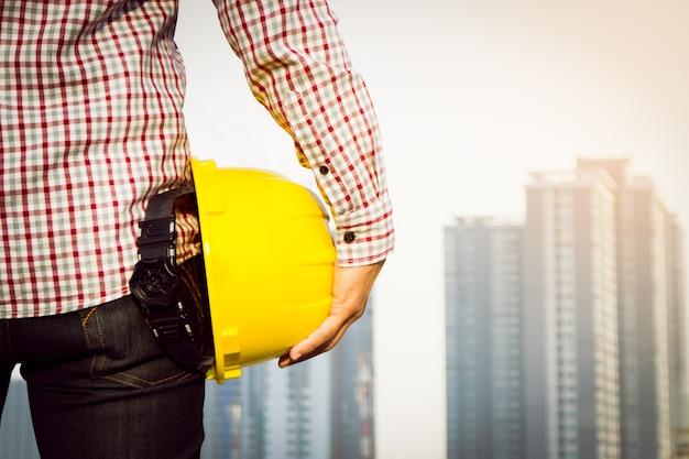 Hand ingenieur arbeiter mit gelben schutzhelm mit gebäude vor ort hintergrund. Kostenlose Fotos