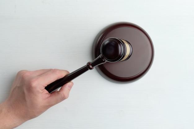 Hand klopft mit einem richterhammer auf den tisch Premium Fotos