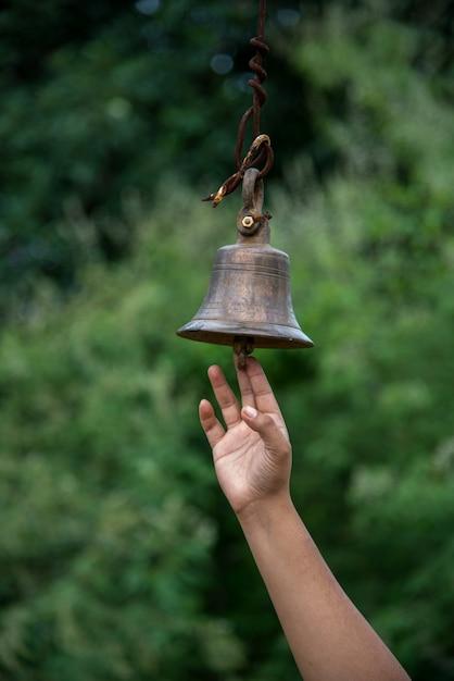Hand läutete eine große glocke am tempel. draußen Premium Fotos