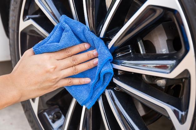 Hand mit blauem mikrofaserstoffreinigungs-autorad. Premium Fotos