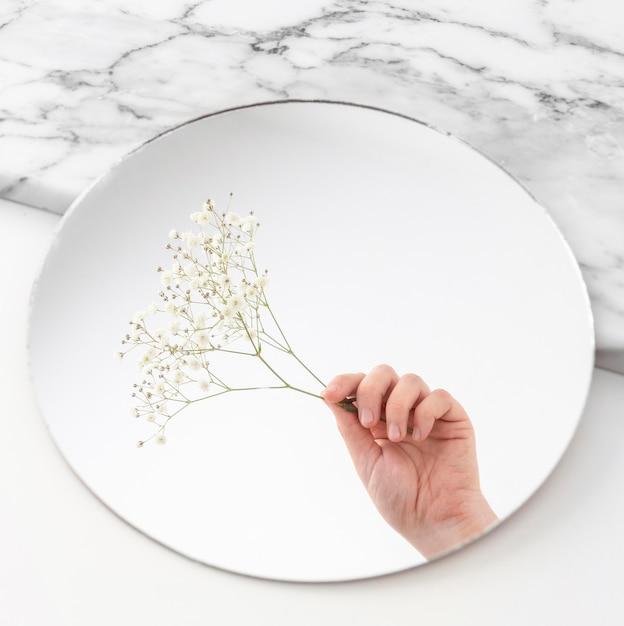 Hand mit blumen im spiegel Kostenlose Fotos