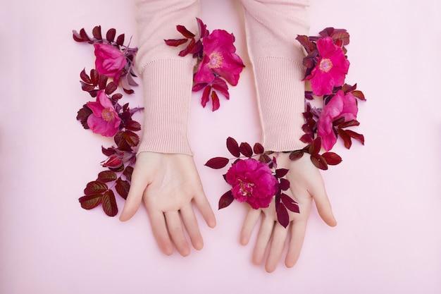Hand mit den rosa blumen und blumenblättern, die auf einer papierwand, kosmetik für handhautpflege liegen. natürliche blütenkosmetik, ätherische öle, anti-falten- und anti-aging-handpflege Premium Fotos