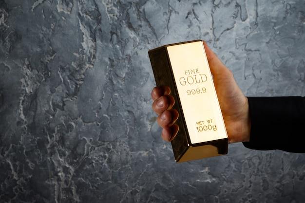 Hand mit einem goldbarren Premium Fotos