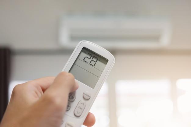 Hand mit fernbedienung auf klimaanlage im raum gerichtet Premium Fotos