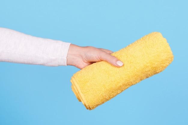 Hand mit gefaltetem gelbem handtuch isoliert Premium Fotos