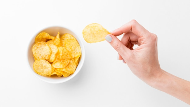 Hand mit kartoffelchips Premium Fotos