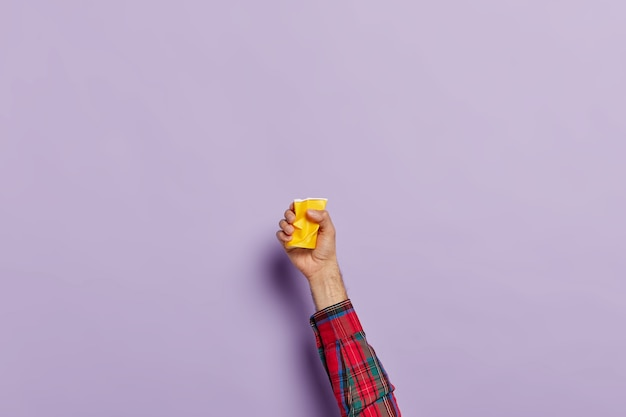 Hand mit leerer zerknitterter tasse kaffee über lila Kostenlose Fotos