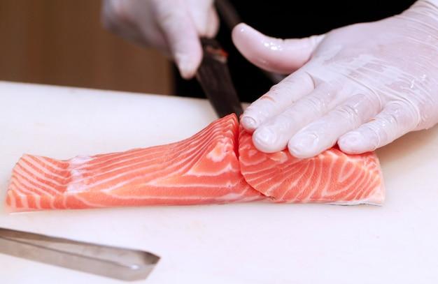 Hand mit messer schneidet lachsfische. rohfische auf dem kochen des brettes. chef bereitet rohen fisch für jap vor Premium Fotos