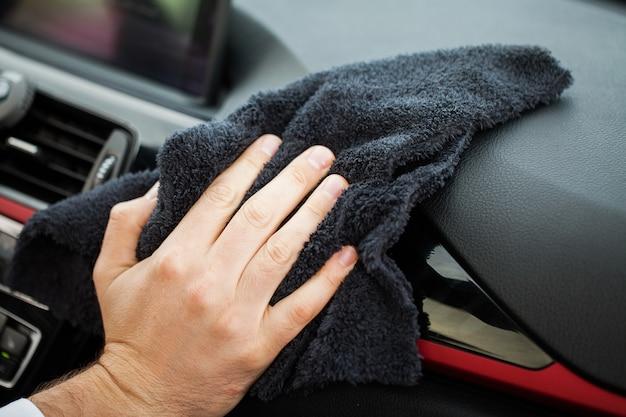 Hand mit mikrofasertuchreinigungs-autoinnenraum Premium Fotos