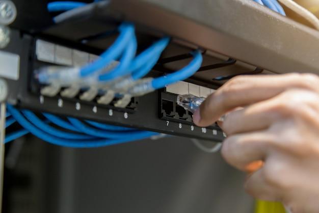 Hand mit netzwerkkabeln, die an server in einem datencenter angeschlossen sind Premium Fotos