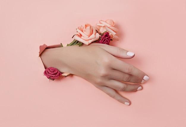 Hand mit papierblumen und gemalten nägeln wird durch ein loch im papierhintergrund gestoßen Premium Fotos