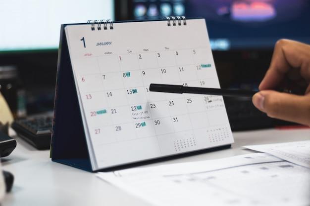 Hand mit stiftspitze auf kalenderseite Premium Fotos