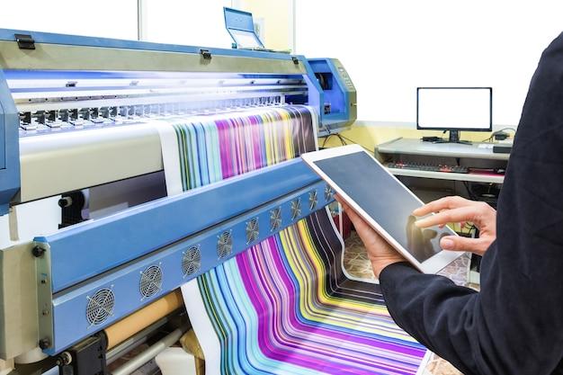 Hand mit tablet-steuerung mit tintenstrahldrucker, der mehrfarbiges vinyl druckt Premium Fotos