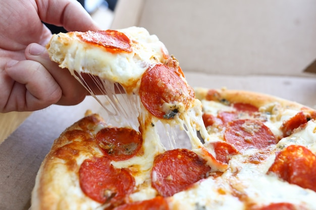 Hand nimmt ganze heiße käsepizza aus der schachtel. Premium Fotos