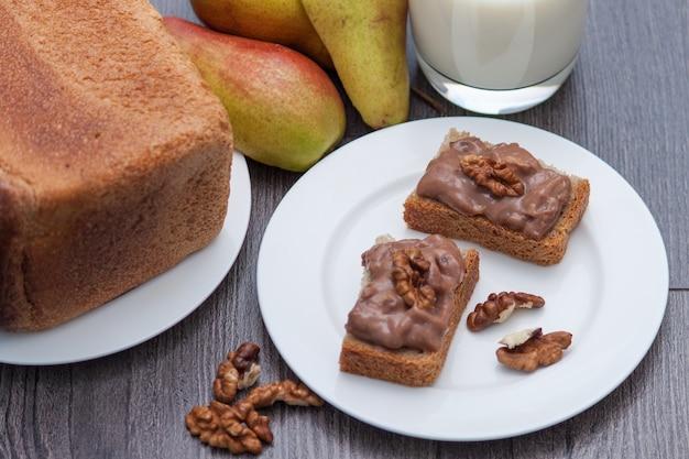 Hand- oder hausgemachte schokoladenpaste mit nüssen. gesunder snack. milch, birne, brot. Premium Fotos
