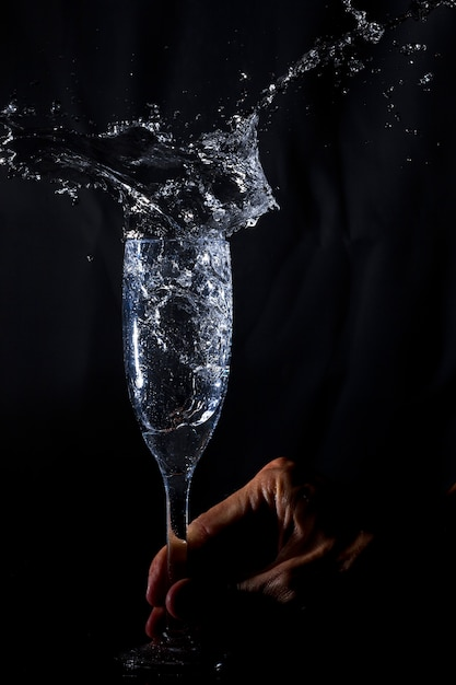 Hand schüttelt ein glas mit wasser Kostenlose Fotos