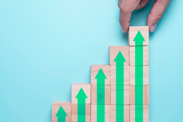 Hand setzen holzwürfel block, die bildschirm erhöhen oder grünen pfeil nach oben drucken. es ist ein symbol für das wachstum des wirtschaftlichen investitionsgewinns. Premium Fotos