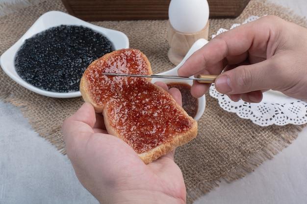 Hand slathers marmelade auf brot mit messer. Kostenlose Fotos