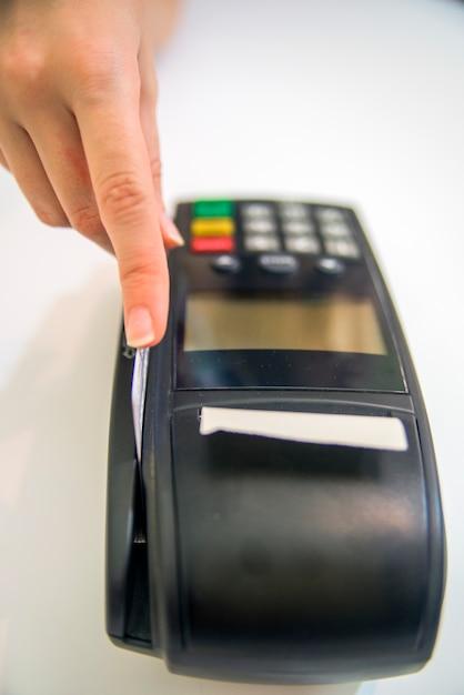 Hand swiping kreditkarte im speicher. weibliche hände mit kreditkarte und bank-terminal. farbe bild von einem pos und kreditkarten. Kostenlose Fotos