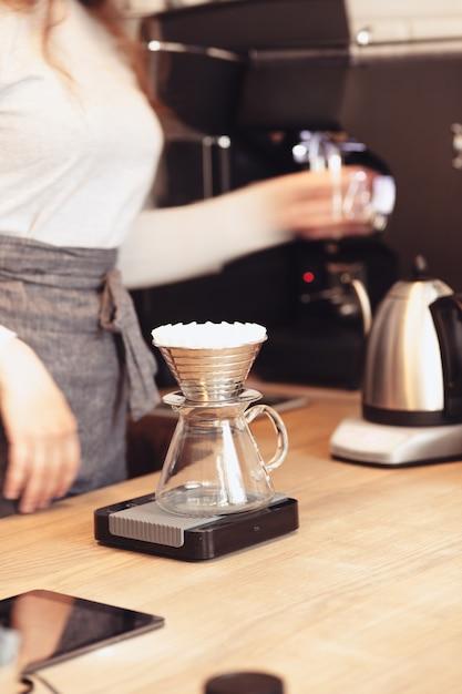 Hand tropft kaffee, barista gießt wasser auf kaffeesatz mit filter Kostenlose Fotos