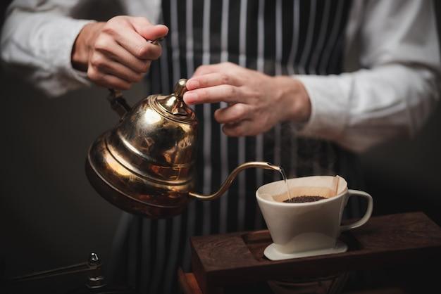 Hand tropft kaffeefilter, barista gießt heißes wasser auf gerösteten kaffeepulver mit filter Premium Fotos