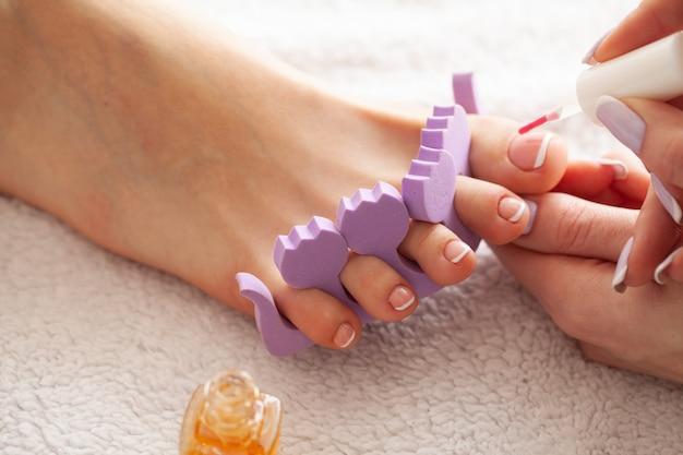 Hand- und nagelpflege. die füße der schönen frauen mit pediküre im schönheitssalon. der meister, der auf nagel aufträgt. spa maniküre Premium Fotos