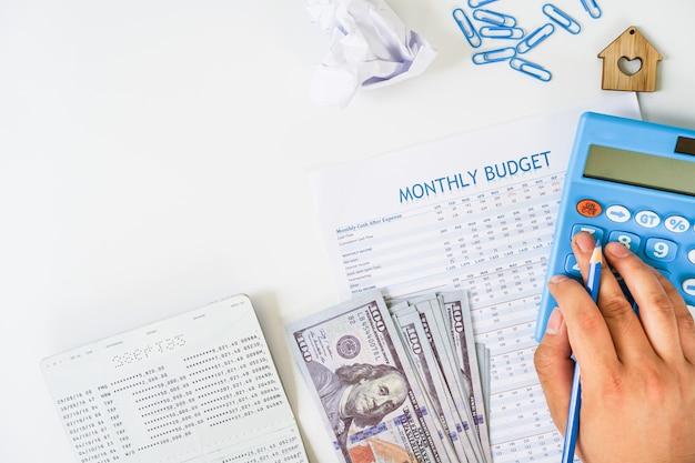 Hand unter verwendung des taschenrechners, der monatsbudget mit sparbuch berechnet und us-banknotenebene lag auf weißem hintergrund. Premium Fotos