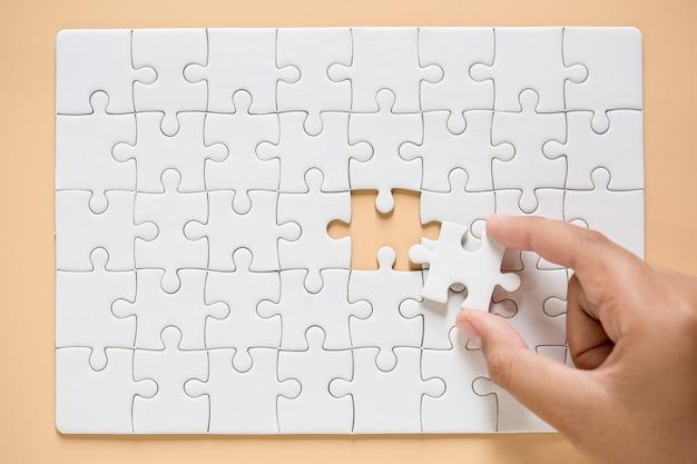 Hand verbinden puzzleteile auf tabellenhintergrund Kostenlose Fotos