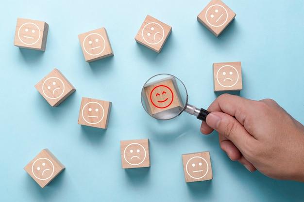 Hand verwenden lupe, um glück emotion zwischen traurigkeit und regelmäßige stimmung zu finden. kundenzufriedenheit und bewertung nach service oder marketing-umfrage. Premium Fotos