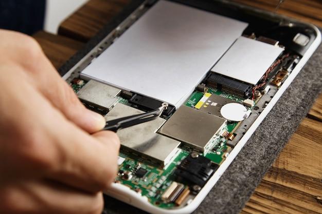 Hand verwendet eine pinzette, um eine kleine crew aufzunehmen, die die batterie auf dem motherboard hält. reparieren eines defekten elektronischen dienstes Kostenlose Fotos