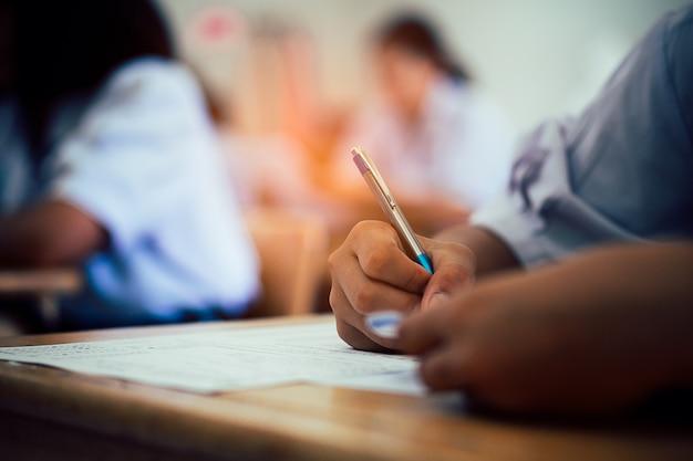 Hand von den studenten, die prüfung mit druck im klassenzimmer nehmen Premium Fotos