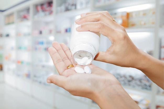 Hand von doktor medizinflasche auf medizinschrank und speichermedizin und apothekendrogerie halten Premium Fotos