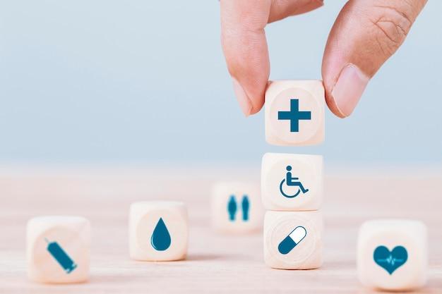Hand wählt ein medizinisches symbol des emoticonikonen-gesundheitswesens auf holzklotz-, gesundheitswesen- und krankenversicherungskonzept Premium Fotos