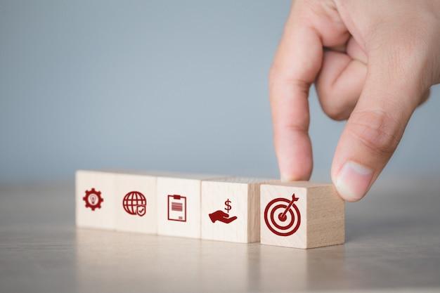 Handanordnung des blockierens von holzblöcken mit symbolpfeil und geschäft, das auf das geschäftskonzept abzielt. Premium Fotos