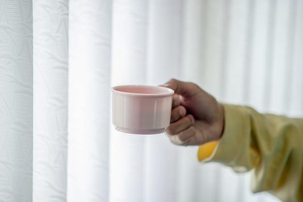 Handbild und kaffeetasse trinkendes konzept des kaffees Premium Fotos