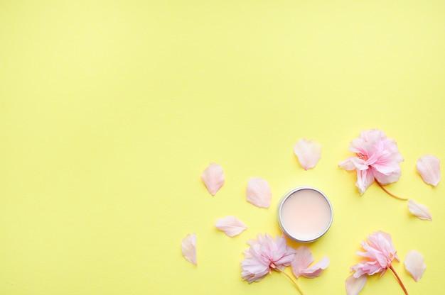 Handcreme, lippenbalsam und seife auf einem gelben hintergrund. Premium Fotos