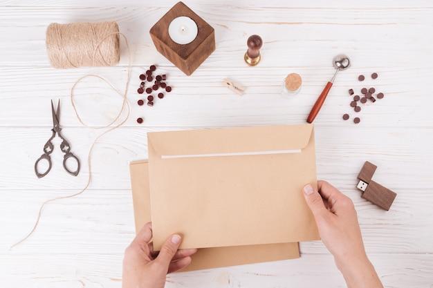 Hände mit Umschlag nahe Satz von Scheren, Drehungen, Kerze und USB-Stick Kostenlose Fotos